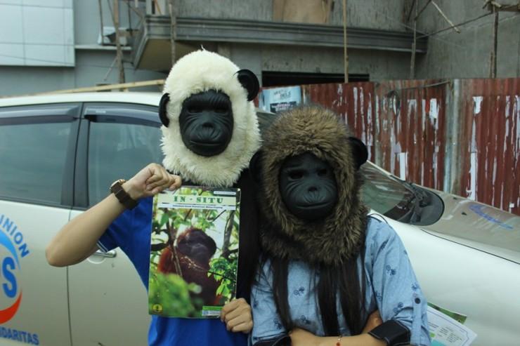 peserta hari orangutan sedunia memakai topeng orangutan