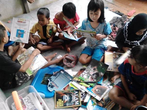 Semangat dan keceriaan anak-anak membaca buku tentang lingkungan dan satwa. Foto dok. Yayasan Palung
