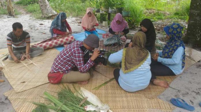 Perajin tikar pandan sedang menganyam dan diliput salah satu media nasional. Yayasan Palung.jpeg