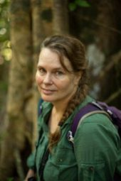 Orangutan researcher Cheryl Knott in the forest by a large strangler fig tree in Gunung Palung